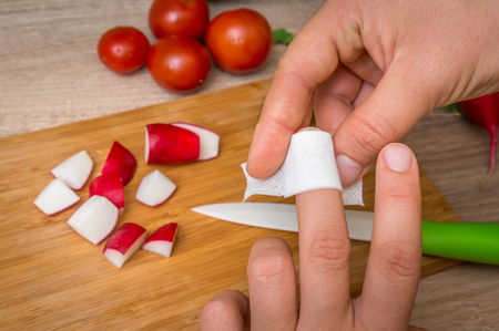 Woman is applying plaster on her finger - injury in kitchen