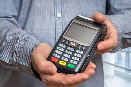 Photo pour Payment terminal in hand of man - bank money transfer concept - image libre de droit