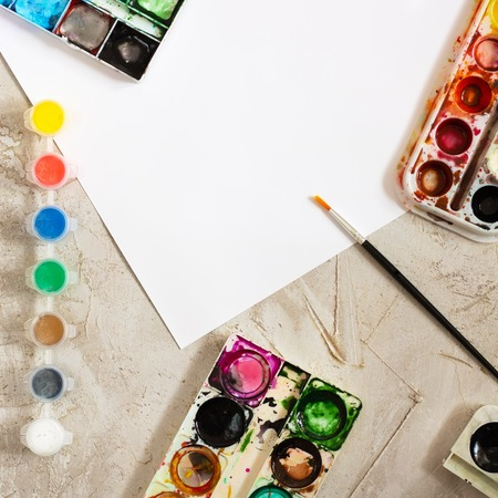 Foto de Flatlay with bright paints in small round containers and many palettes, brush and white sheet of paper on grey cement backcground, Workspace, Mess, Artist, drawing, Hobby, Art, Square, Frame, Place for work - Imagen libre de derechos