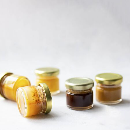 Five Small glass jar with metal cap with different kinds and colours of honey put in line isolate and on grey cement background with copy space. Healthy product, natural. Squareの写真素材