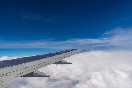 Photo pour Wing of a plane flying above the clouds - image libre de droit