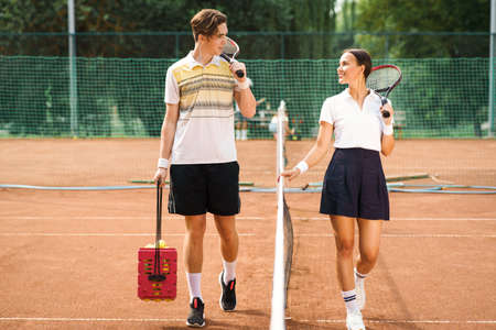 Young cheerful couple walking on the tennis court before the game. Male and female players on the tennis court