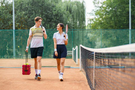 Young couple on tennis court. Two tennis players are walking around the court and talking