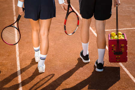 Couple with rackets and balls on a tennis court