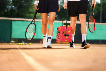 Couple leaving the tennis court carrying equipment after the game is over. Tennis game concept