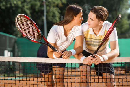 Photo pour Young couple flirting with each other while standing on the tennis court after the game - image libre de droit