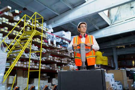 Photo pour Warehouse worker operates a pallet loader - image libre de droit