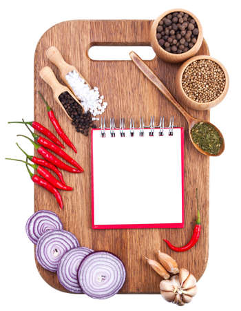 Open notebook and fresh vegetables on an old wooden cutting board  Isolated on white