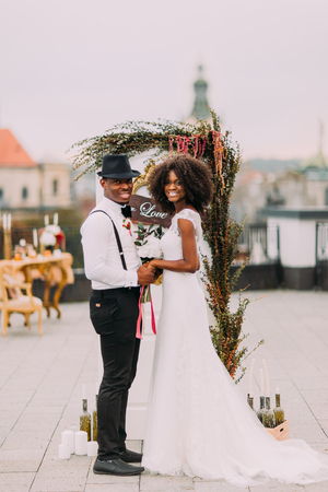 Photo pour Happy african wedding couple smiling and holding hands on the rooftop. - image libre de droit