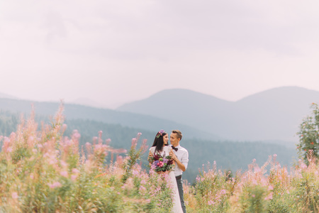 Young happy wedding couple on the meadow in Alps. Honeymoon.