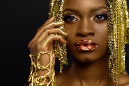 Foto de Sexy african american female model with glossy makeup and golden wig. Face art - Imagen libre de derechos