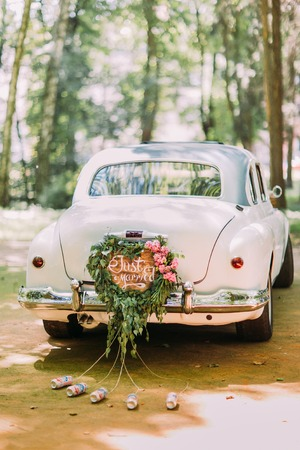 Photo pour Bumper of retro car with just married sign and cans attached. - image libre de droit
