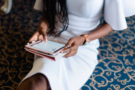 sexy body of black woman in white dress. she is taking a tablet in her hands chatting in internet. Blue carpet in luxury vip hotel. Classic furniture.