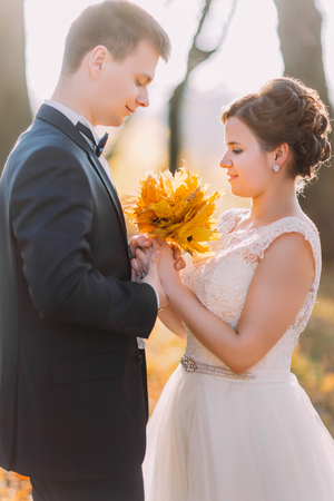 Sensitive vertical portrait of the newlyweds. The bride is holding the bouquet of yellowed leaves.