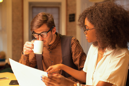 Handsome man and african american woman working together. Woman holding graphics and talking to the man, man drinking coffee or tea.