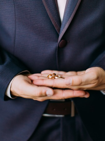 Vertical view of the hands of the groom holding the golden wedding rings