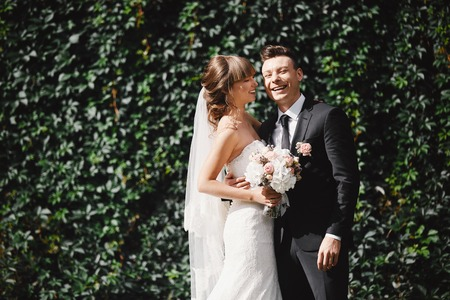 Photo pour Closeup Portrait of wedding bride and groom with bouquet posing by the old cathedral. Bridal couple, Happy Newlywed woman and man hugging. Bride and groom - image libre de droit