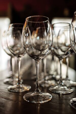 Photo pour empty wine glasses. Beautiful new glasses for wine from glass stand in even rows on a wooden table in a restaurant. selective focus - image libre de droit