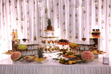 Photo pour Fresh, exotic, organic fruits, light snacks in a plate on a buffet table. Assorted mini delicacies and snacks, restaurant food at event. Decorated delicious table for a party goodies. - image libre de droit