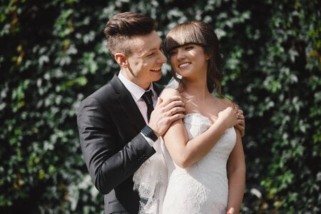 Foto für Amazing smiling wedding couple. Pretty bride and stylish groom. groom and bride posing in front wall with green ivy. - Lizenzfreies Bild