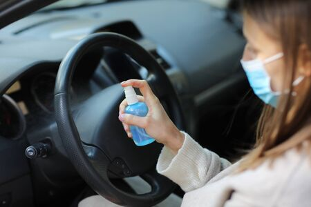Foto de Spraying anti-bacterial sanitizer spray on hand in car, infection control concept. Sanitizer to prevent Coronavirus, Covid-19, flu. Spray bottle. womanwearing in medical protective mask driving a car - Imagen libre de derechos