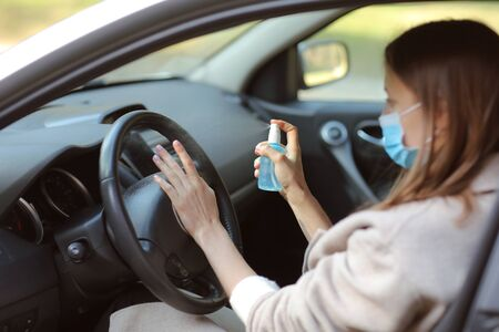 Photo pour Spraying anti-bacterial sanitizer spray on hand in car, infection control concept. Sanitizer to prevent Coronavirus, Covid-19, flu. Spray bottle. womanwearing in medical protective mask driving a car - image libre de droit