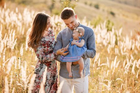 Photo pour mom, dad and little girl having fun outdoors in the grass on summer day. mothers, fathers and babys day. Happy family for a walk. - image libre de droit