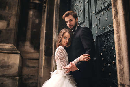 Photo pour Young stylish newlyweds are hugging behind old rustic wooden door. wedding day - image libre de droit