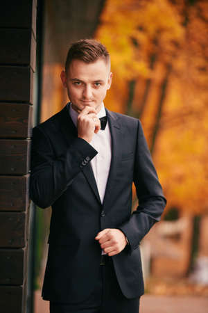 Foto de stylish young groom in a black suit in the autumn park on wedding day. - Imagen libre de derechos
