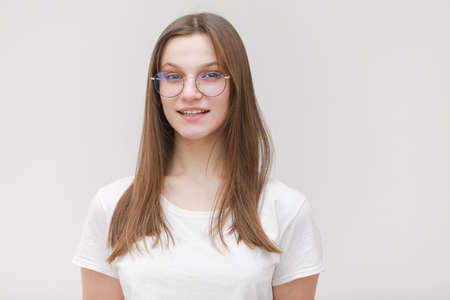 Photo for pretty teenage girl in glasses having fun on a white background. female in white t shirt with long hair in studio. - Royalty Free Image