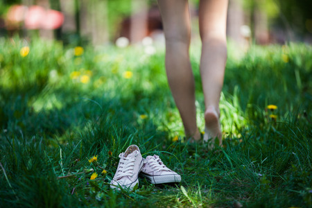 Foto de Woman walking barefoot on the green grass, shoes in focus, shallow DOF - Imagen libre de derechos