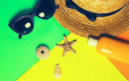 Beach accessories on a bright neon colorful background. Dried starfish, a fragment of a straw hat and sea urchin shell, a bottle of sunscreen lotion and  sunglasses . Summer vacation background. Image is with copy space