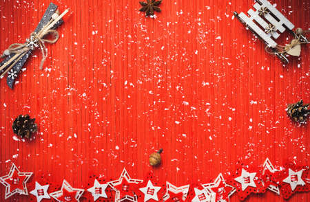 Foto de Winter composition with decorative sledge and ski, star anise, acorn, pine cones, colorful felt stars on a red background. Top view. Image is with copy space - Imagen libre de derechos