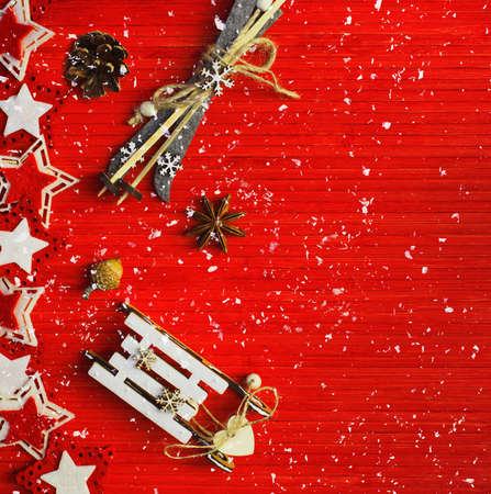 Foto de Winter composition with star anise, acorn, pine cone, colorful felt stars, decorative sledge and ski on a red background. Top view. Image is with copy space - Imagen libre de derechos