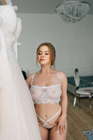 Portrait of a bride with a big bust in white lace underwear