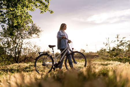 Photo for A young woman is walking near a bicycle in a city park at summer sunset. Blurred background with copy space area for text. - Royalty Free Image
