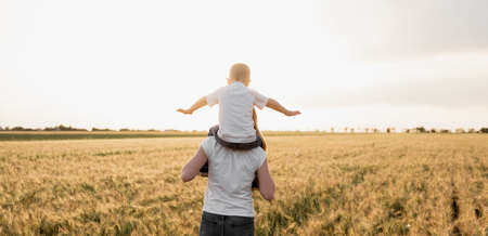 Photo pour very happy family of mother and son having fun outdoors at summer sunset. warm light. woman with a child in nature. Wheat field. Place for text. Banner - image libre de droit