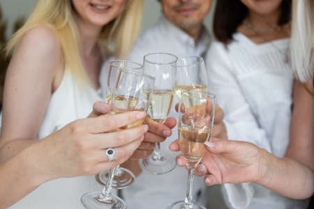 Photo pour Close-up of friends hands holding glasses of champagne and making cheers. Corporate concept at work. - image libre de droit