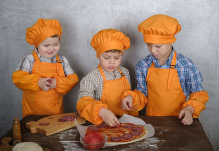 three cute European boys in costumes chefs enthusiastically busy cooking pizza. three brothers help mom to cook pizza with sausage and cheese