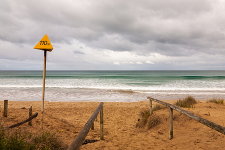 An electrical hazard warning sign at the beach, Use caution at the beach