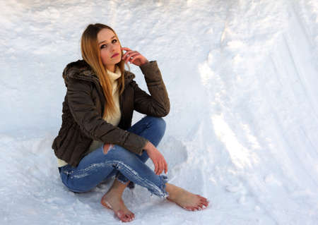 Pensive and sad barefoot girl with long blond hair sitting in the snow dreaming about something.の写真素材
