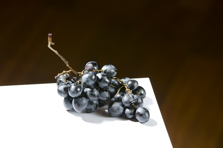 blue spoiled grapes on a white board