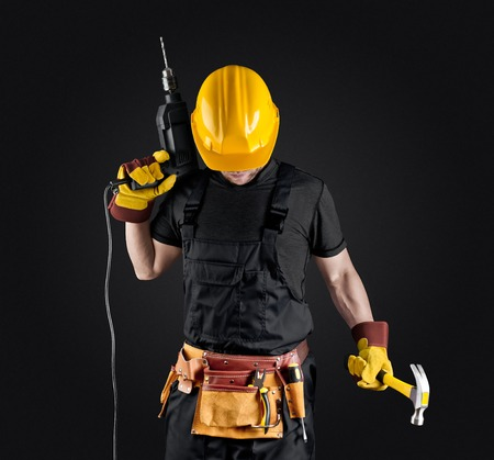 construction worker in helmet with hammer and drill on dark background