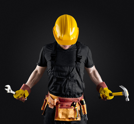 construction worker in helmet with hammer and wrench on dark background