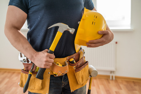 Photo pour construction worker with tool belt, helmet and hammer - image libre de droit