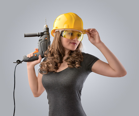 Photo pour worker girl in a helmet with a drill on a gray background - image libre de droit