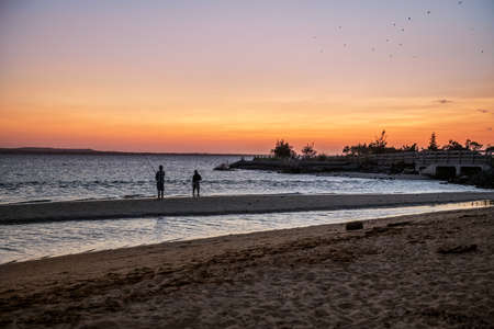 Photo pour Two men fishing on the bay at sunset on Sandy Hook along the Jersey shore. - image libre de droit
