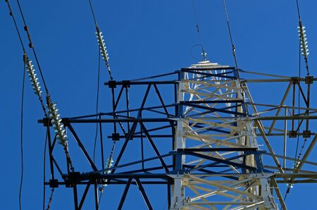 Photo for White metal construction is power electricity transmission tower with cables against a blue sky - Royalty Free Image