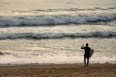 Surfer wading into sea fist pumping
