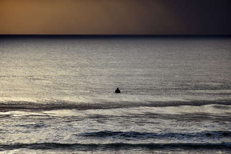 Surfer waiting for a wave at dawn